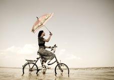 La ragazza va per un giro del ciclo all'acqua Immagini Stock Libere da Diritti