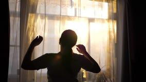 La ragazza va primo mattino alla finestra, apre le tende I raggi del ` s del sole attraversano il vetro e illuminano la stanza stock footage