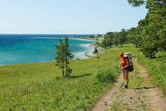 La ragazza va su una pista circa il lago Baikal Fotografia Stock