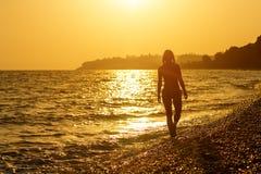 La ragazza va su una spiaggia al tramonto Fotografia Stock Libera da Diritti