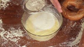 La ragazza vaglia la farina sopra la pastella, primo piano stock footage