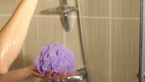 La ragazza versa il gel della doccia sulla spugna porpora, primo piano video d archivio