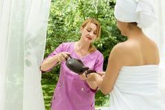 La ragazza versa il tè dopo la stazione termale Fotografia Stock Libera da Diritti