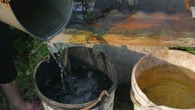 La ragazza versa l'acqua nel secchio La donna cade la catena con il secchio nel pozzo rustico per estrarre l'acqua archivi video