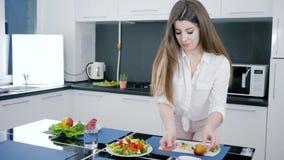 La ragazza versa l'olio d'oliva su insalata fresca con la verdura al rallentatore alla cucina, pasto sano archivi video
