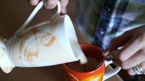 La ragazza versa la bevanda del caffè da una tazza in una tazza video d archivio