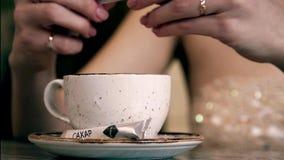 La ragazza versa lo zucchero nella tazza di caffè archivi video
