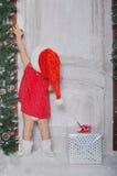 La ragazza vestita come Santa apre la porta sotto neve Immagini Stock Libere da Diritti