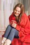 La ragazza vestita in maglione bianco e jeans tricottati coperti in involucro rosso sta sedendosi con una tazza rossa della bevan fotografia stock libera da diritti