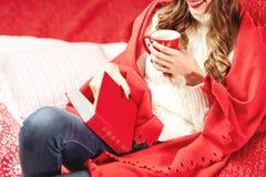 La ragazza vestita in maglione bianco e jeans tricottati coperti in involucro rosso sta sedendosi con una tazza rossa della bevan immagine stock