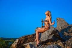 La ragazza vestita in un bikini fuma un narghilé su un pendio di collina Fotografie Stock