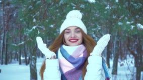 La ragazza in vestiti caldi dell'inverno sorride sulla macchina fotografica in una foresta dell'inverno archivi video