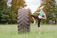 La ragazza in vestiti di sport sta colpendo la gomma con il suo ginocchio Allenamento della via Immagine Stock