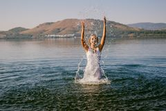 La ragazza in vestito bianco bagna nell'estate del lago fotografia stock libera da diritti