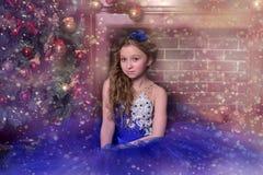 La ragazza in vestito blu si siede dal camino Immagini Stock