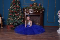 La ragazza in vestito blu si siede dal camino Fotografia Stock Libera da Diritti