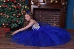 La ragazza in vestito blu si siede dal camino Immagine Stock Libera da Diritti