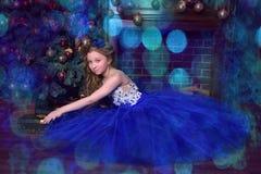 La ragazza in vestito blu si siede dal camino Fotografia Stock