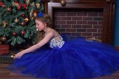 La ragazza in vestito blu si siede dal camino Fotografie Stock Libere da Diritti
