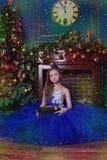 La ragazza in vestito blu si siede dal camino Fotografie Stock