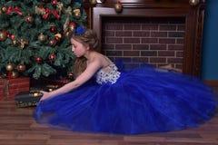 La ragazza in vestito blu si siede dal camino Immagini Stock Libere da Diritti