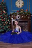 La ragazza in vestito blu si siede dal camino Immagine Stock