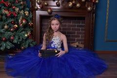 La ragazza in vestito blu si siede dal camino a natale Fotografie Stock Libere da Diritti