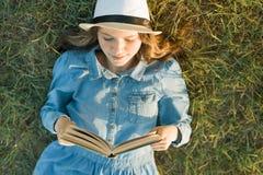 La ragazza in vestito e cappello si trova sul libro di lettura dell'erba verde Vista da sopra immagine stock