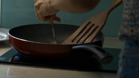 La ragazza in vestito gira i pancake saporiti sulla grande pentola video d archivio