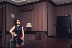 La ragazza in vestito nero con il braccialetto rosso fatto a mano, annerisce gli orecchini e la borsa tricottati fotografia stock