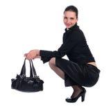 La ragazza in vestito nero con il sacchetto si siede. Immagini Stock Libere da Diritti