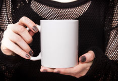 La ragazza in vestito nero sta tenendo la tazza bianca Modello per progettazione dei regali di Halloween Fotografia Stock Libera da Diritti