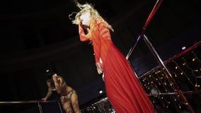 La ragazza in vestito rosso, scarpe da tennis balla sul supporto sul partito in night-club Cubisti stock footage