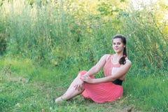 la ragazza in vestito rosso sta sedendosi sull'erba immagini stock