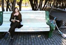 La ragazza in vetri con capelli lunghi ed il libro si siedono sul banco in parco Immagini Stock