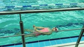 La ragazza in vetri di nuoto nuota sulle loro parti posteriori in una piscina Bambino di sport video d archivio