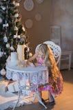 La ragazza vicino ad un albero di Natale con un coniglio favorito del giocattolo scrive una lettera a Santa, le scatole, il Natal Fotografia Stock Libera da Diritti
