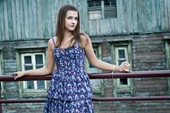 La ragazza vicino ad una casa di legno Fotografie Stock Libere da Diritti
