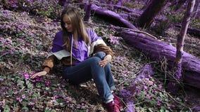 La ragazza viola della foresta di favola in un rivestimento lilla si siede nel ciclo polare e li esamina in una foresta lilla fav stock footage