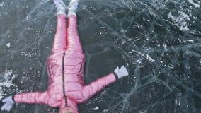 La ragazza vola e rotola sul ghiaccio La giovane coppia si diverte durante la passeggiata dell'inverno contro fondo di ghiaccio d video d archivio