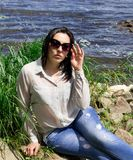 La ragazza XXL più la donna di modello di sorriso della sponda del fiume di dimensione si rilassa immagine stock