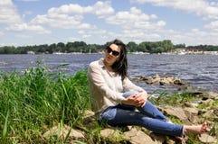 La ragazza XXL più la donna di modello di sorriso della sponda del fiume di dimensione si rilassa fotografie stock libere da diritti