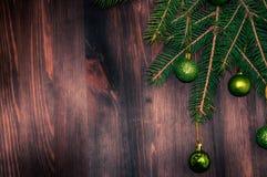 La rama comió con las bolas del ` s del Año Nuevo en un fondo de madera marrón Imagen de archivo