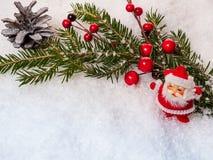 La rama de árbol de navidad con el cono del pino y Santa Claus figuran en la nieve blanca Foto de archivo