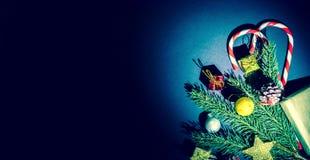 La rama de un árbol de navidad con las bolas, los conos de abeto, los caramelos tradicionales y las cajas con los regalos encendi fotografía de archivo