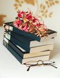 La rama del árbol de castaña rosado está en la pila de libros con los vidrios en la tabla blanca, foco selectivo Fotografía de archivo