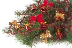 La rama del árbol de navidad con las agujas cortas adornó las campanas y los arcos aislados en el fondo blanco Imágenes de archivo libres de regalías