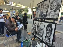 La Rambla, Barcelona, December 2015-street artist drawing caricature of man Royalty Free Stock Photos