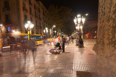La Rambla, Barcelona, Spain. Night time on La Rambla, busy tourism area long exposure image blurs people and street vendors selling the illicit wares to passing Royalty Free Stock Image