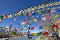 La rangée de drapeau de prière sur le pont croisent plus de le fleuve Indus Photographie stock libre de droits